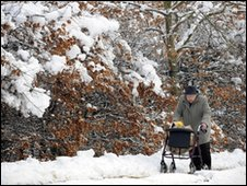 Elderly woman makes her way home through the snow in Hartley Wintney, Hampshire