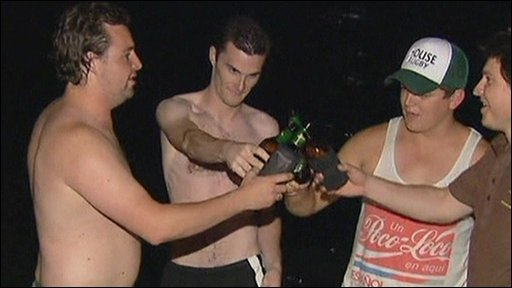 Men drinking beer on the beach at night