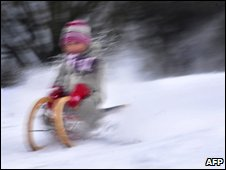 Girl whizzing down snowy slope