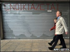 People walking past a closed shop in Athens