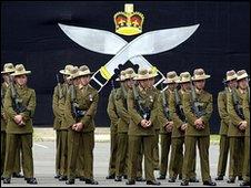 Gurkha soldiers in front of kukri emblem
