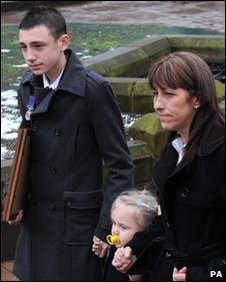 L/Cpl Kirkness's brother Christopher and mother Margaret hold the hand of his daughter Brooke after his funeral service