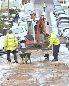 Workers lay grit after a burst water main flooded an icy road in Bristol