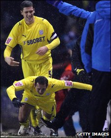 Michael Chopra's goal celebrations appear to be cut short by the foot of Robins boss Gary Johnson
