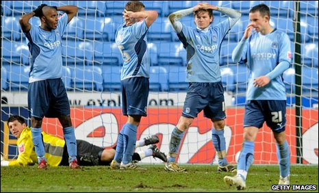 Coventry players show their disappointment after Portsmouth scored a late winner
