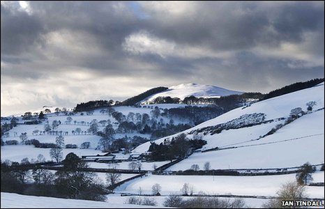 Clwydian Range covered in snow and with ominous clouds overhead