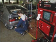 Mechanic works on a car in a garage