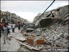 Haitians walk past damaged buildings in Port-au-Prince after a huge earthquake