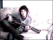 Billy Lockett sitting on a sofa with a guitar