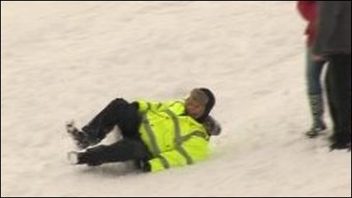 People sledding down snow on tea-trays