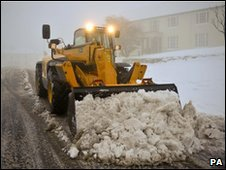 A JCB digger clears snow in Princetown, Devon