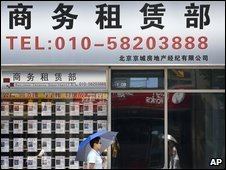 A Chinese woman walks past a property sales office at the Central Business District in Beijing