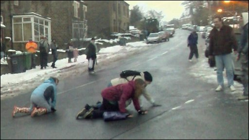 Pedestrians crawl across icy roads