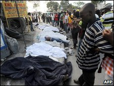 A crowd of people observe the covered corpses of those killed by a massive earthquake in Port-au-Prince on January 13, 2010