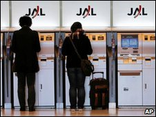 Passengers at Japan Airlines (JAL) check in through a self-check-in machine at Haneda Airport in Tokyo, Japan