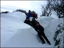 Image of Llyr, Gethin, Cerys, Rhydain and Owain in winter gear standing beside a deep drift of snow - image Enfys Howells