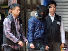 Police inspect the scene of the Causeway Bay acid attack with the suspect (in hood) - 14 January 2010