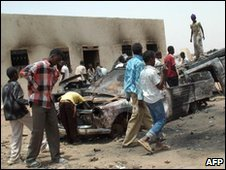 Sudanese gather around a burnt-out car in Sola Aradi, 19/05/2005