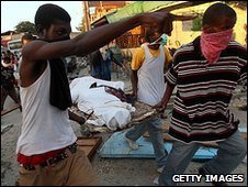 People carry the body of a victim of Haiti's earthquake, 14 January 2010