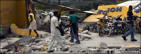 People walk past the remains of collapsed buildings in Haiti (15 January 2010)