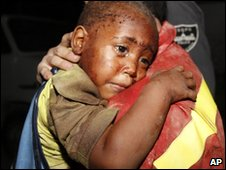 A Spanish rescuer carries a two-year-old boy  after he was rescued from a home that collapsed in Port-au-Prince, Haiti