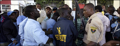 A security guard warns people queueing for fuel in Port-au-Prince (15 January 2010)