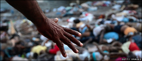 A man gestures towards a pile of dead bodies outside a hospital (15 January 2010)