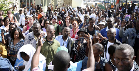 US citizens hold up their passports to gain entry to Port-au-Prince's aiport (15 January 2010)