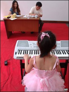 A young Chinese girl taking a piano exam