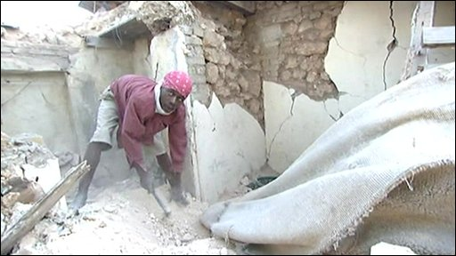 A man tries to dig a body out of the rubble