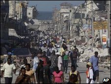 Haitians walk the streets amid collapsed buildings and rubble in downtown Port-au-Prince