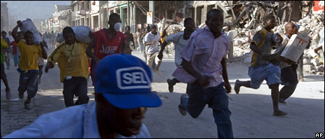People run from the police in Port-au-Prince with supplies from a business
