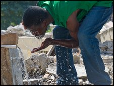 A man drinking from a broken pipe, Haiti, 15 January