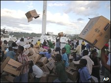 Youths play with empty boxes as they collect them after food was distributed by the World Food Program in Port-au-Prince, Saturday, 16 January 2010