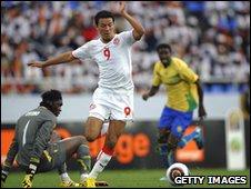 Tunisia's Amine Chemiti (C) rounds Gabon keeper Didier Ovono