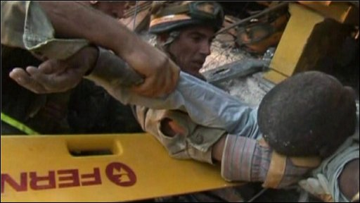 Israeli rescuers pull a man from rubble