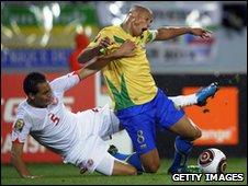Ammar Jemel of Tunisia (L) tackles Gabon's Daniel Cousin
