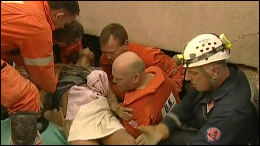 Woman being rescued from rubble in Haiti