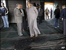 Palestinians inspect fire damage at the Yasuf mosque