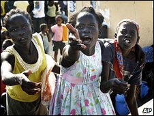 Three Haitian girls reach out for energy bars as they try to get attention of workers - AP Photo/The Miami Herald