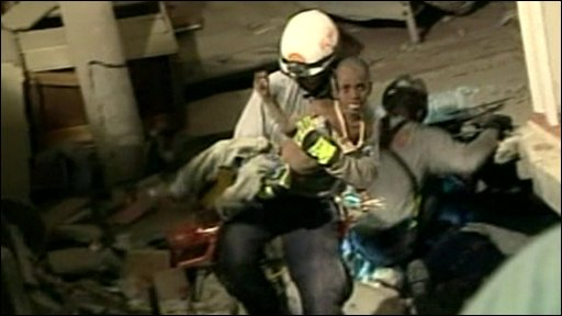 Rescue worker carrys a six-year-old boy from Haiti's rubble