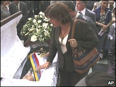 A woman touches the coffin of Venezuela's former President Rafael Caldera during his funeral mass in Caracas, 26 December 2009