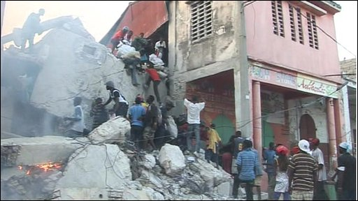 People climb a building in Port-au-Prince