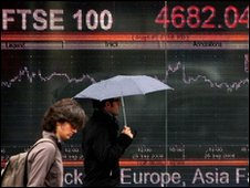 People walks past a video screen in Kensington, London, displaying the FTSE share index
