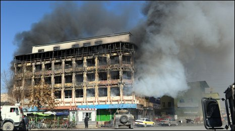 Smoke billows from a shopping mall as Afghan policemen take position in a public market building during clashes between Taliban-linked militants and security forces on January 18, 2010 in Kabul