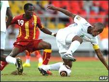 Ghana's Emmanuel Agyemang-Badu (L) and Mady Pananadetiguiri of Burkina Faso (R) vie for the ball