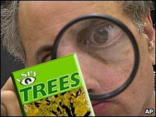 Man uses magnifying glass to look at I-Spy book. (AP Photo/Alan Diaz).