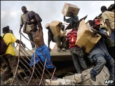 Haitians flee with stolen goods in downtown Port-au-Prince, 19 Jan