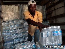 A Haitian aid worker stacks cases of water