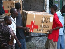 Haitians loading water supplies onto a truck